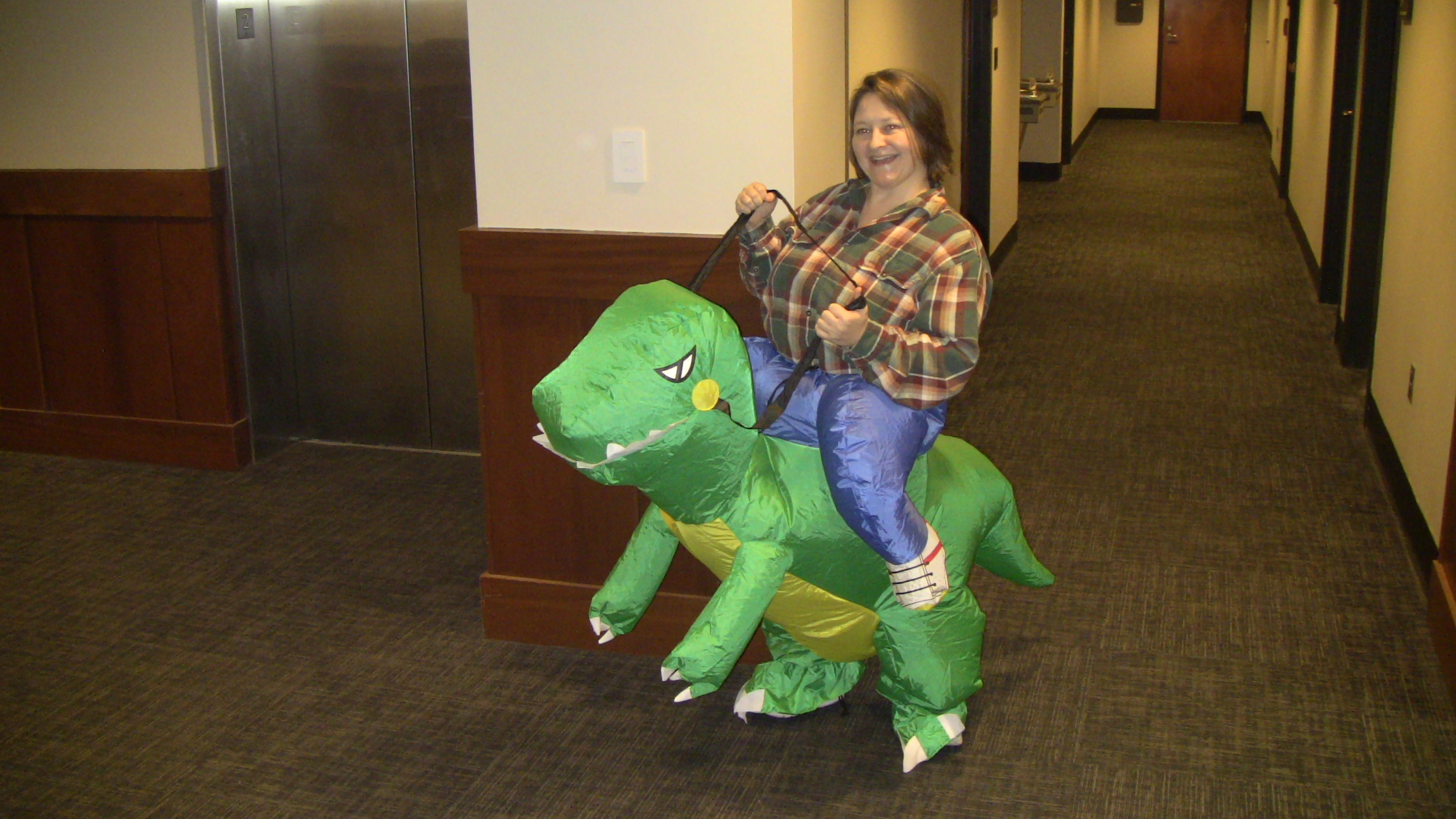 SDS Access Services Advisor, Robin Yekaitis, rides in on her pet dinosaur, Rex, for Halloween.